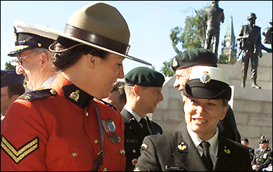 A member of the Royal Canadian Mounted Police and a member of the Canadian Forces prepare Canadian Peacekeeping Service Medals to be presented.
